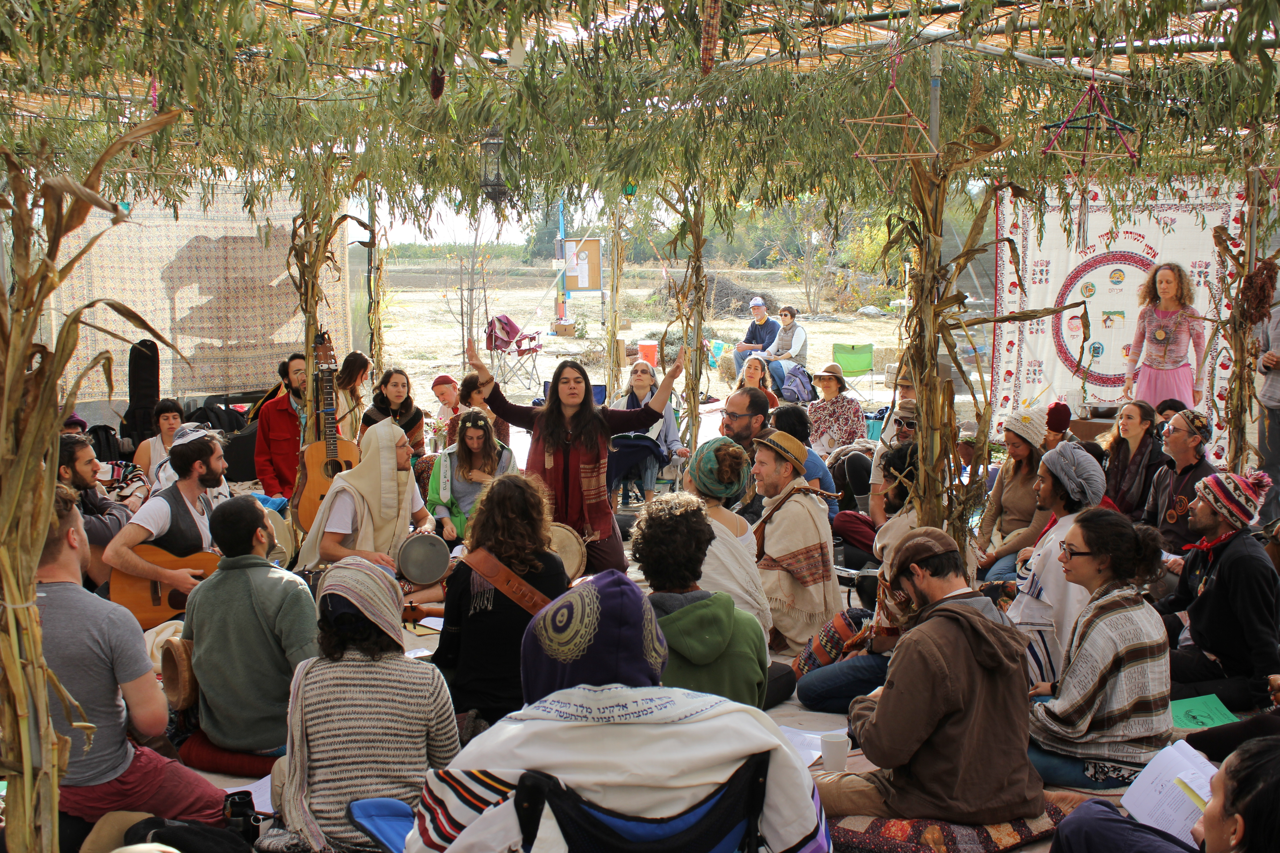 under a very large sukkah, shere raises her hands up as she leads a circle of people in prayer