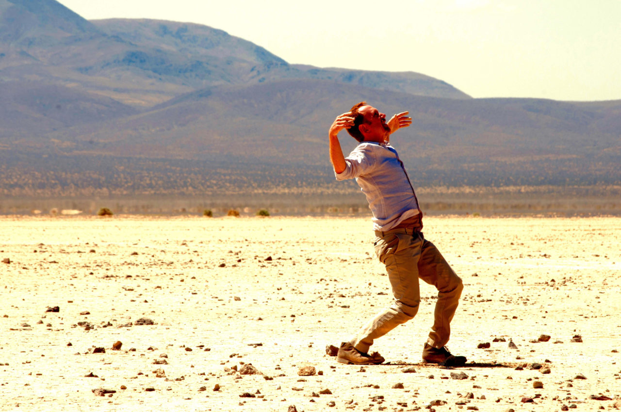 A lone man in a dessert throwing his arms up