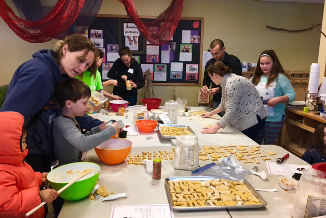 Children and adults sitting around a large table baking