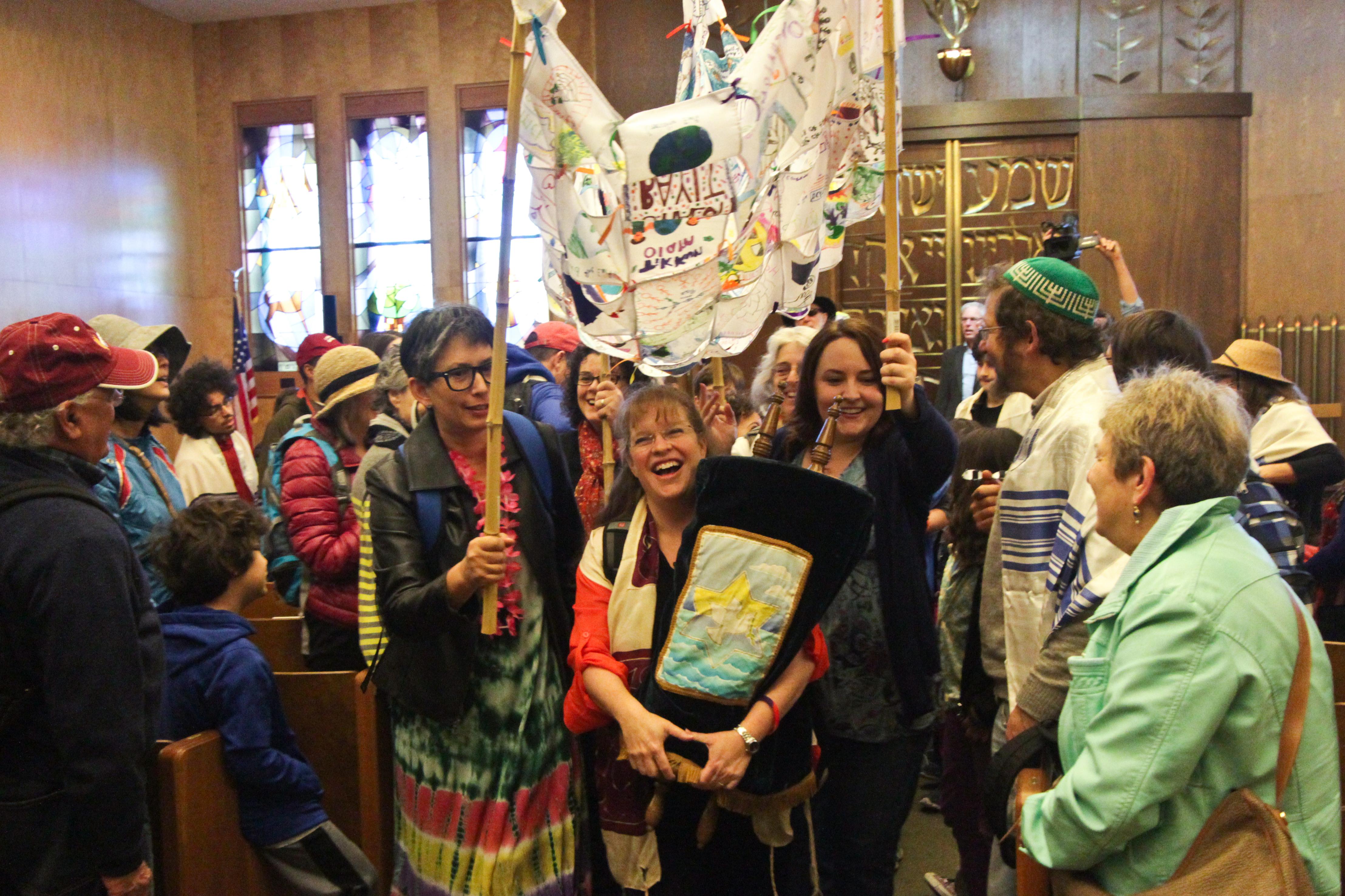 happy Jews carry a Torah under a canopy