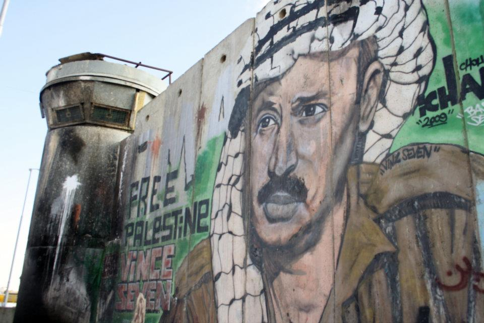Graffiti of the late Palestinian Authority leader Yasser Arafat at the Qalandia Checkpoint between the West Bank and Israel (Photo/Wikimedia Commons)