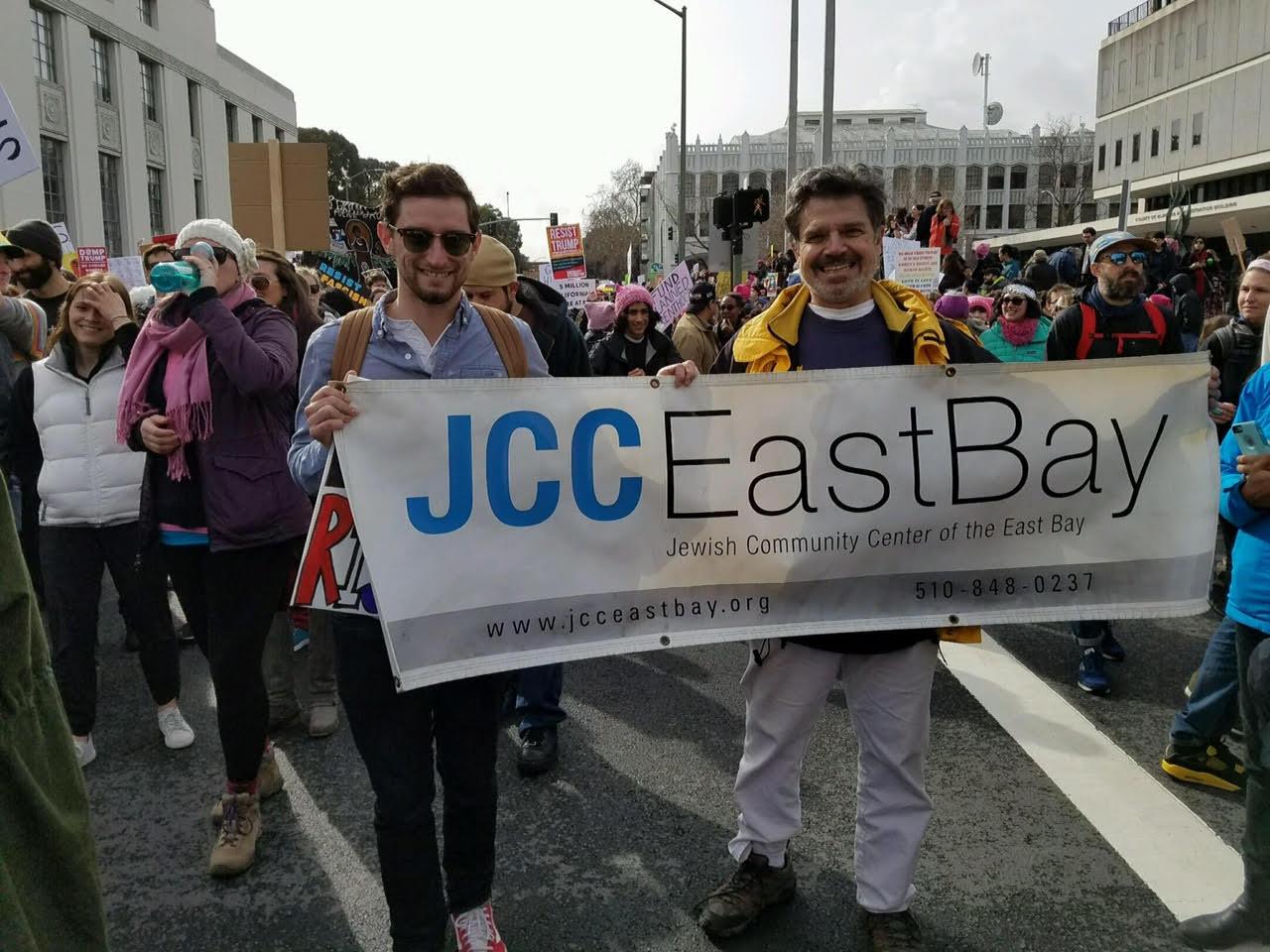 Two men holding a JCC East Bay banner