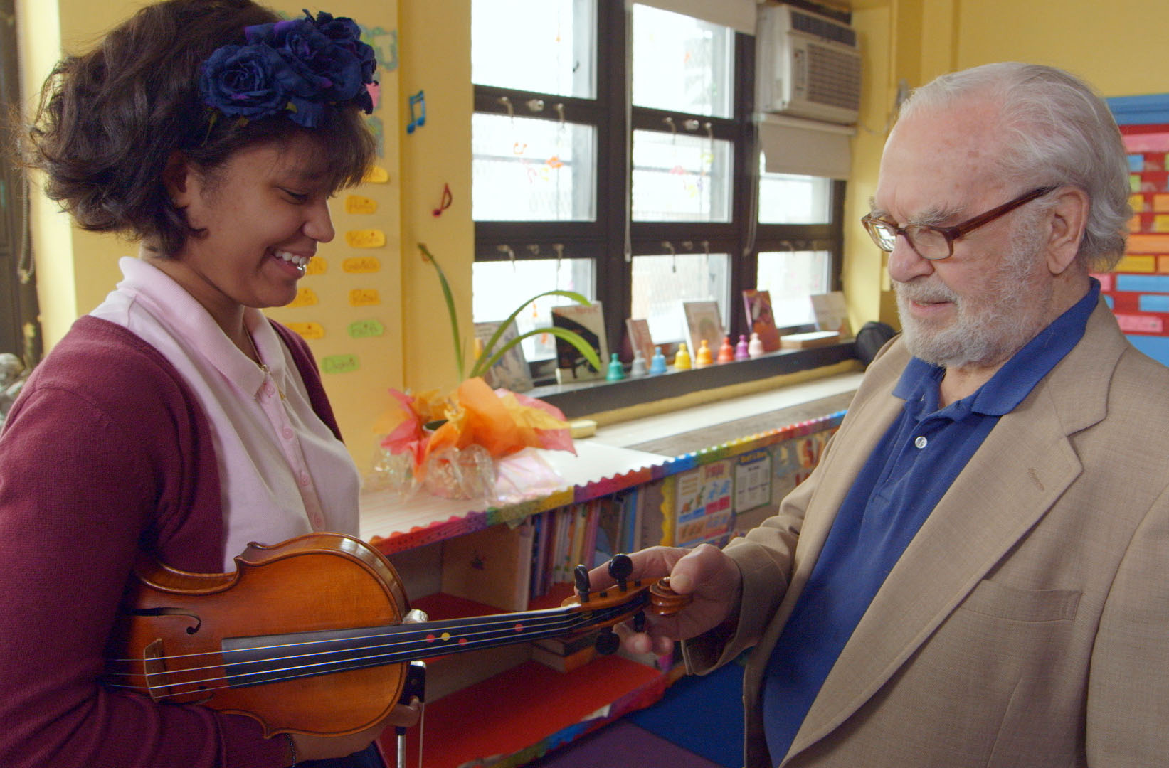 Brianna Perez holds a violin while Joe Feingold looks on
