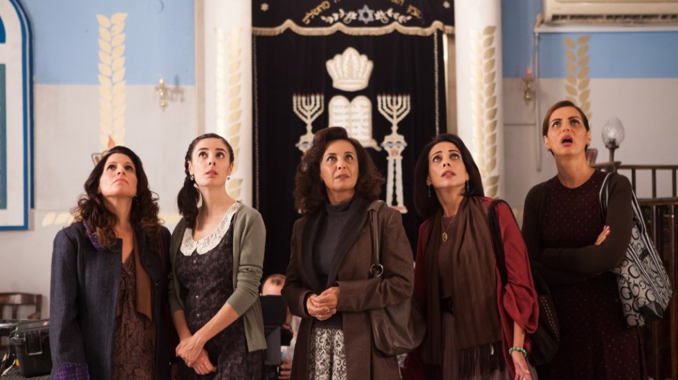 five women stand in a synagogue staring up