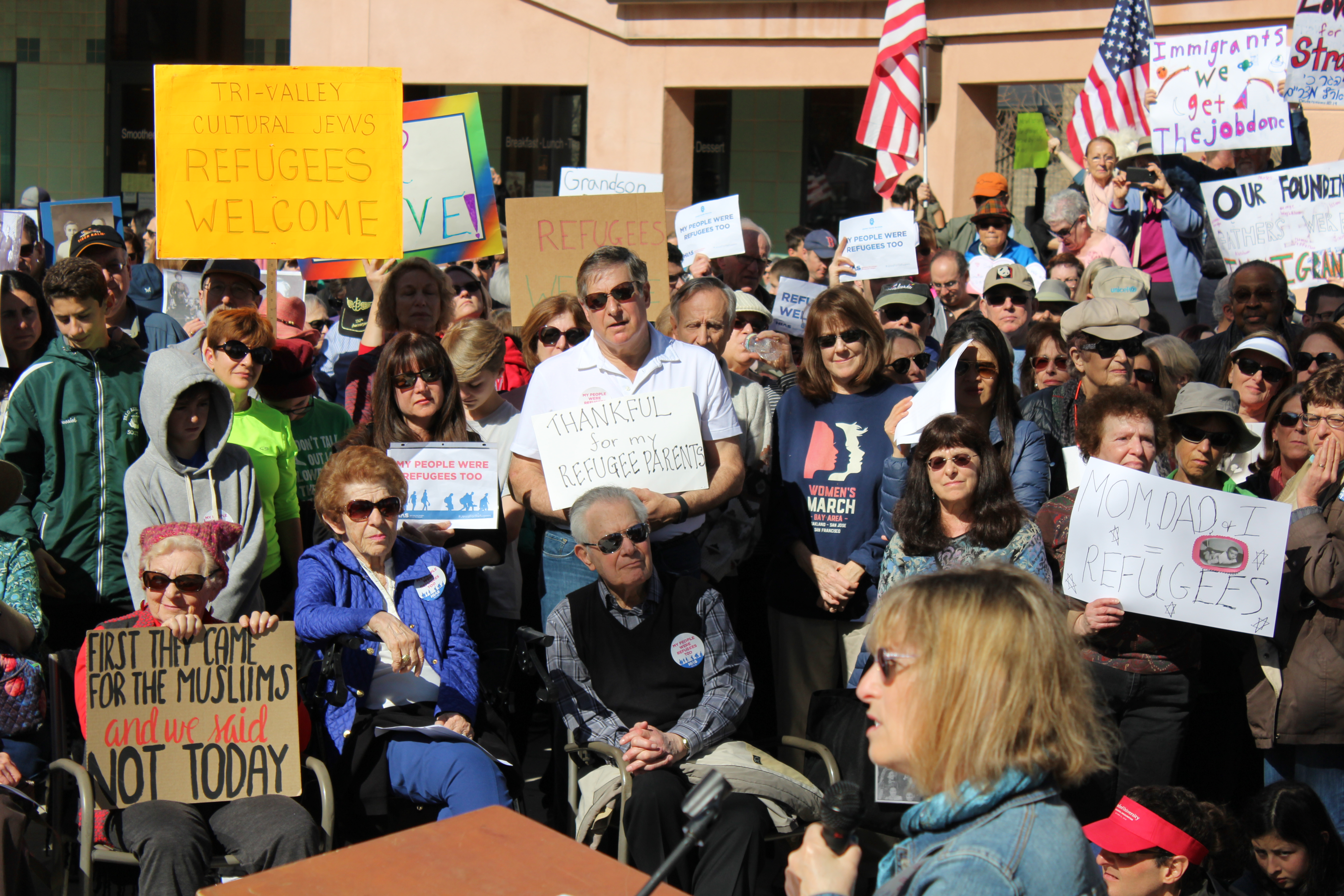 """a large crowd holds signs like """"tri-valley cultural jews: refugees welcome"""""""