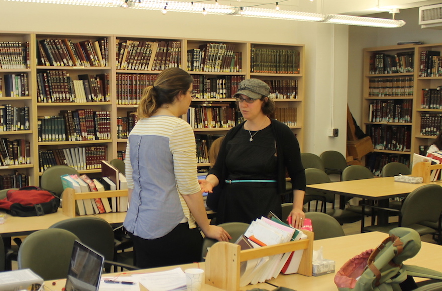 Hurwitz talks to a student in a book-lined yeshiva