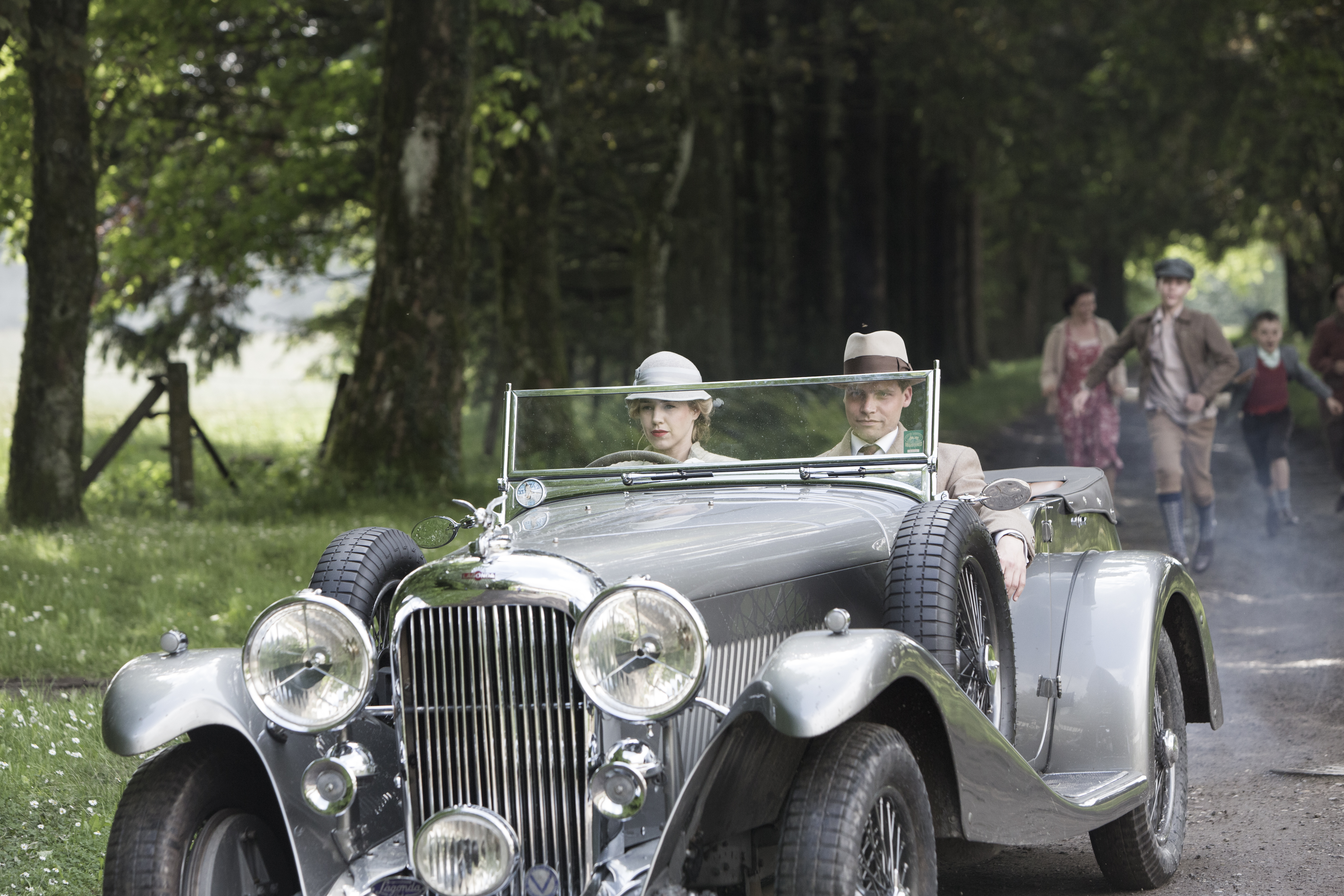 Two people in a 30s-style car