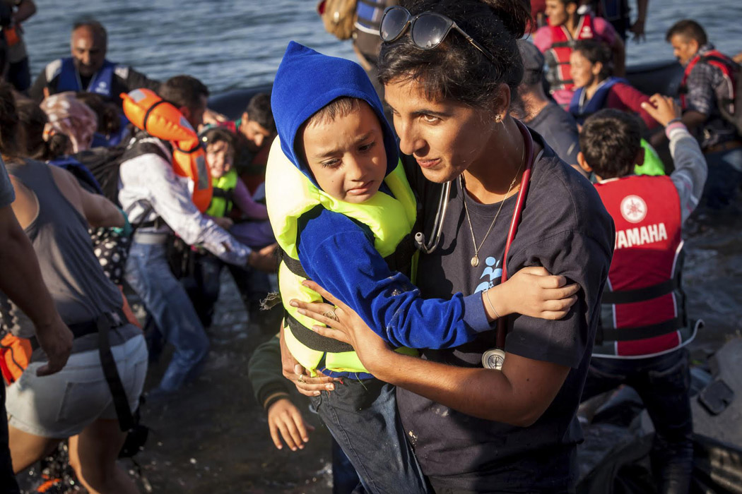 a woman carries a child away from a raft on a beach in Europe
