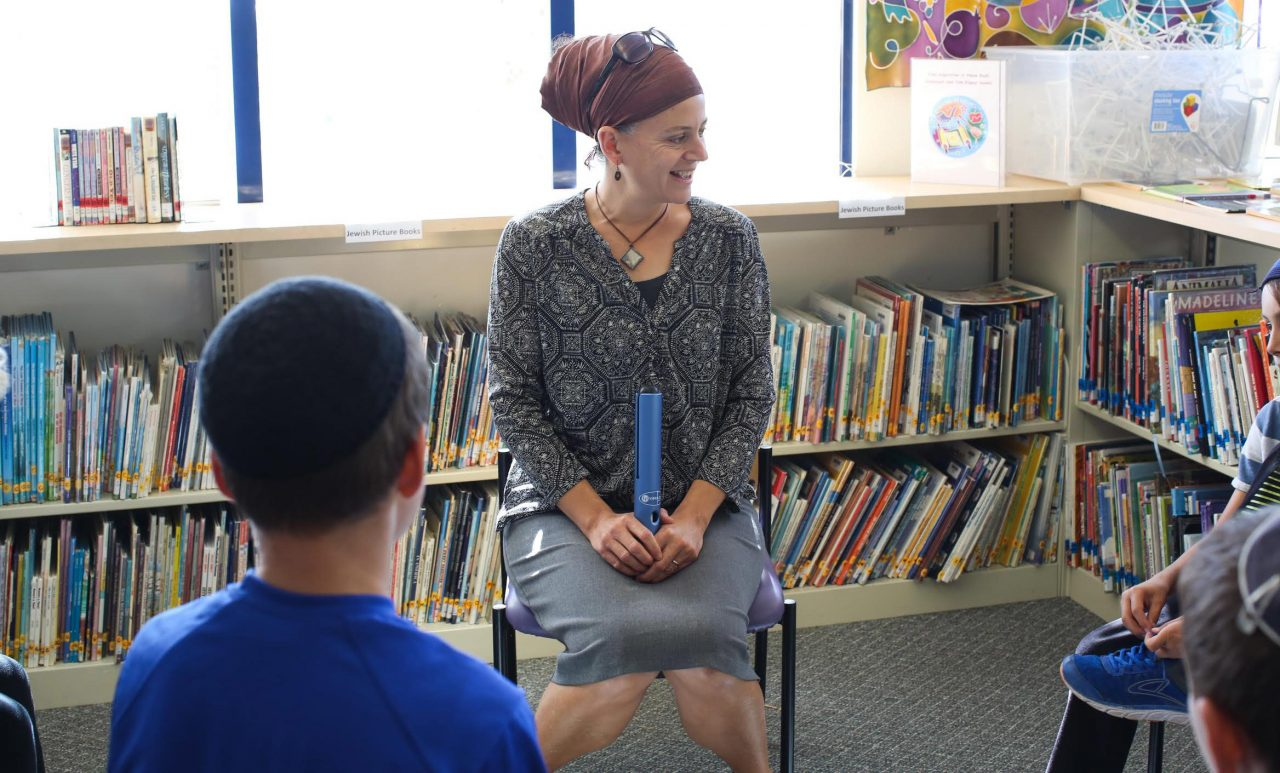 Scwieg sitting in a chair with students