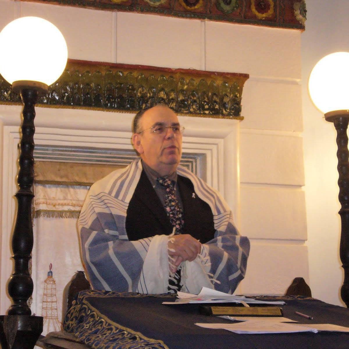 rabbi raj speaking at a podium
