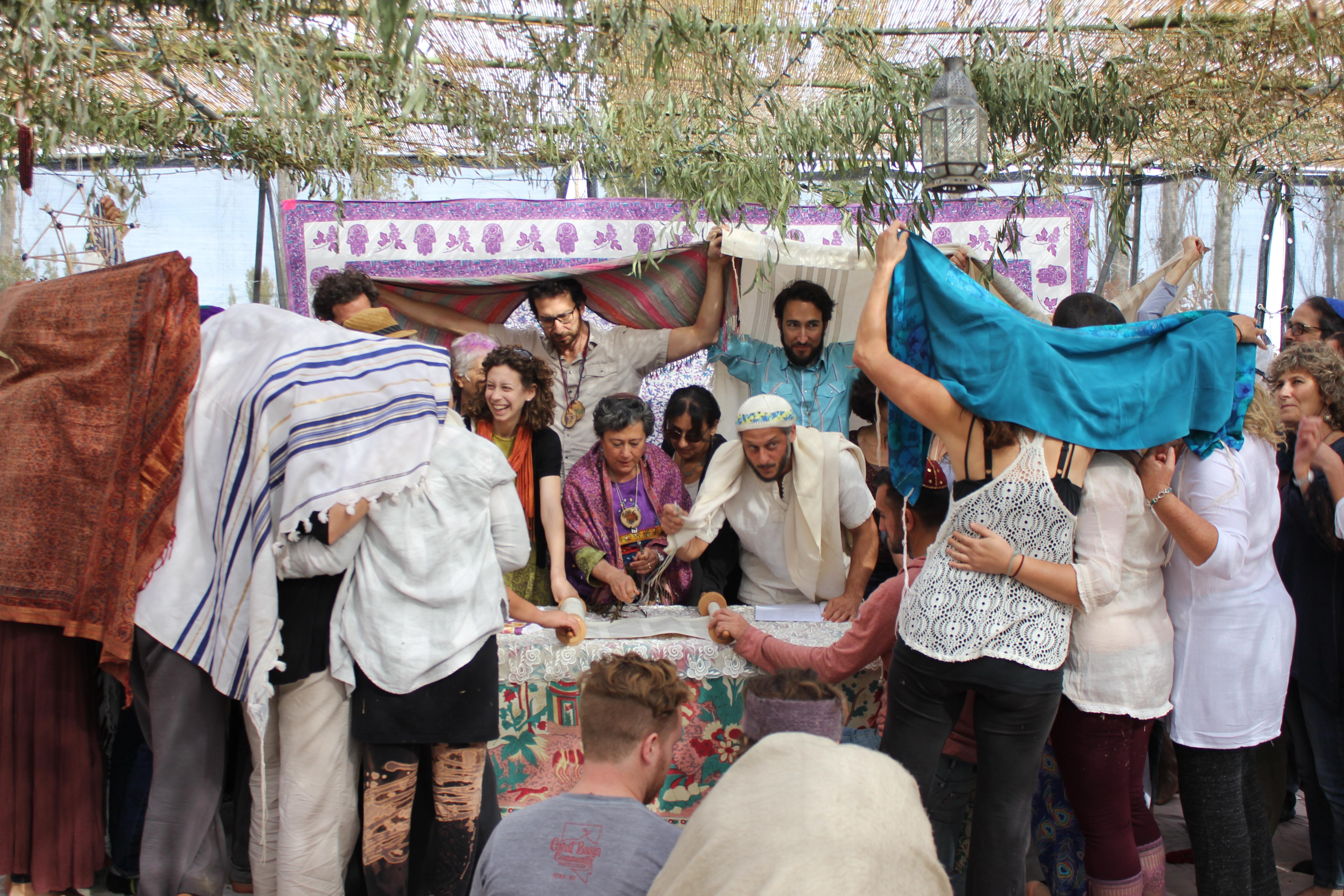 a group of people gather around a torah scroll under a lark sukkah