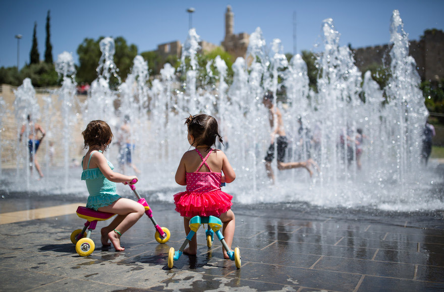 two little girls ride tricycles through a public fountain area