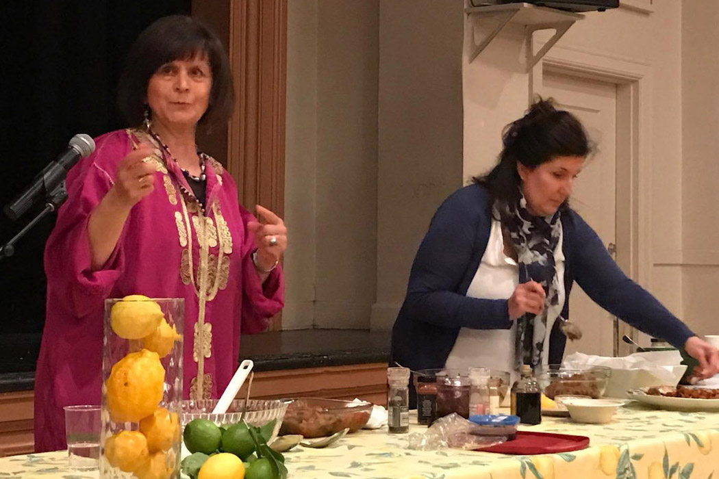 the two women stand before an audience preparing ingredients