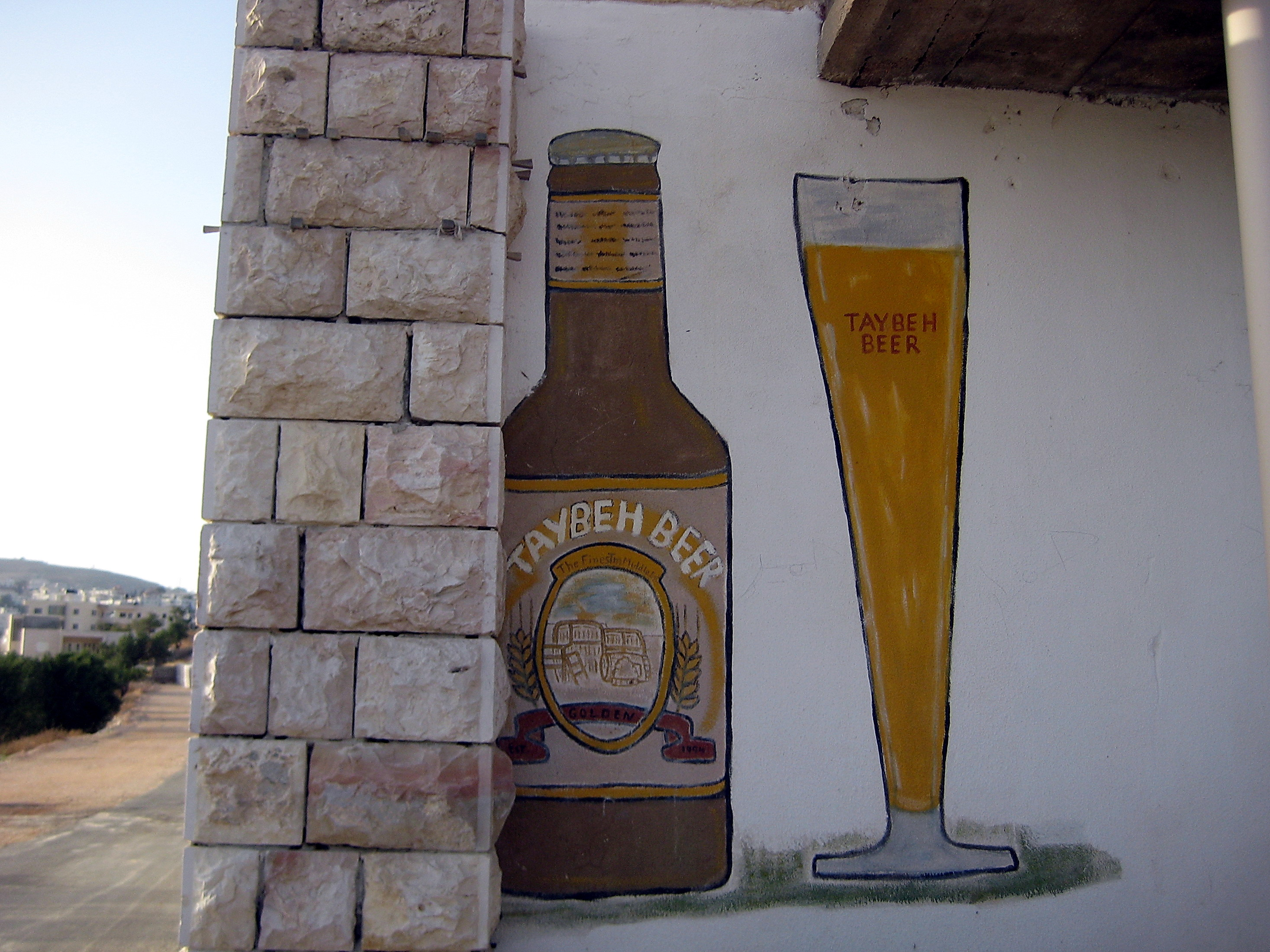 a painting of a bottle of Taybeh beer on a wall