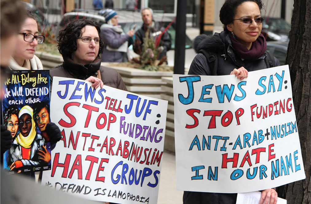 """protesters holding signs like """"Jews tell JUF: Stop funding Anti-Arab/Muslim Hate Groups"""""""