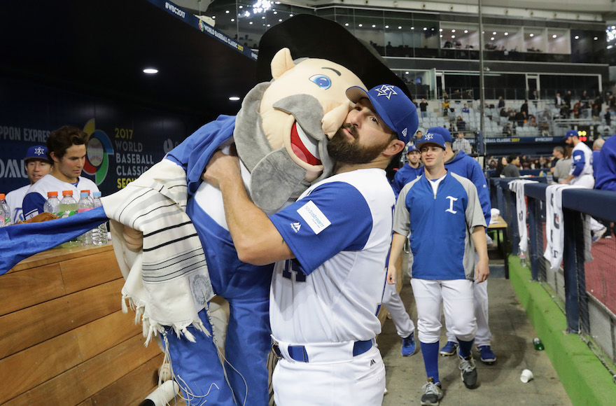 Cody Decker of Team Israel holding team mascot the Mensch on a Bench