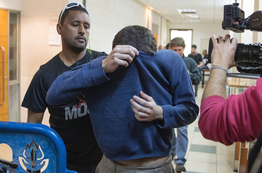 Kaydar covers his face with his shirt as he is led from the courtroom