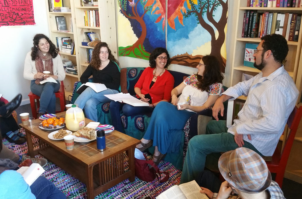 """study participants are seated in a circle in the """"living room"""" area of the studio"""