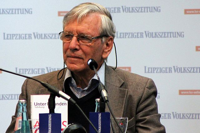 Amos Oz speaking at a microphone