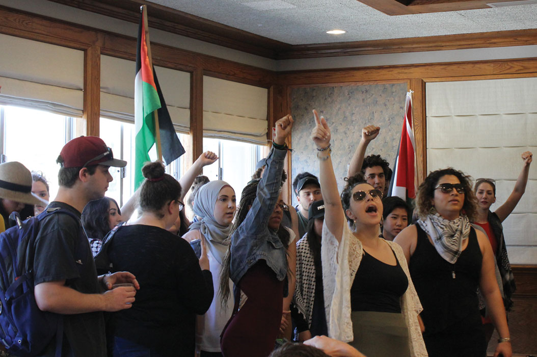 a group of protesters shout and pump their fists in the air. there is a palestinian flag. some of them are wearing keffiyehs