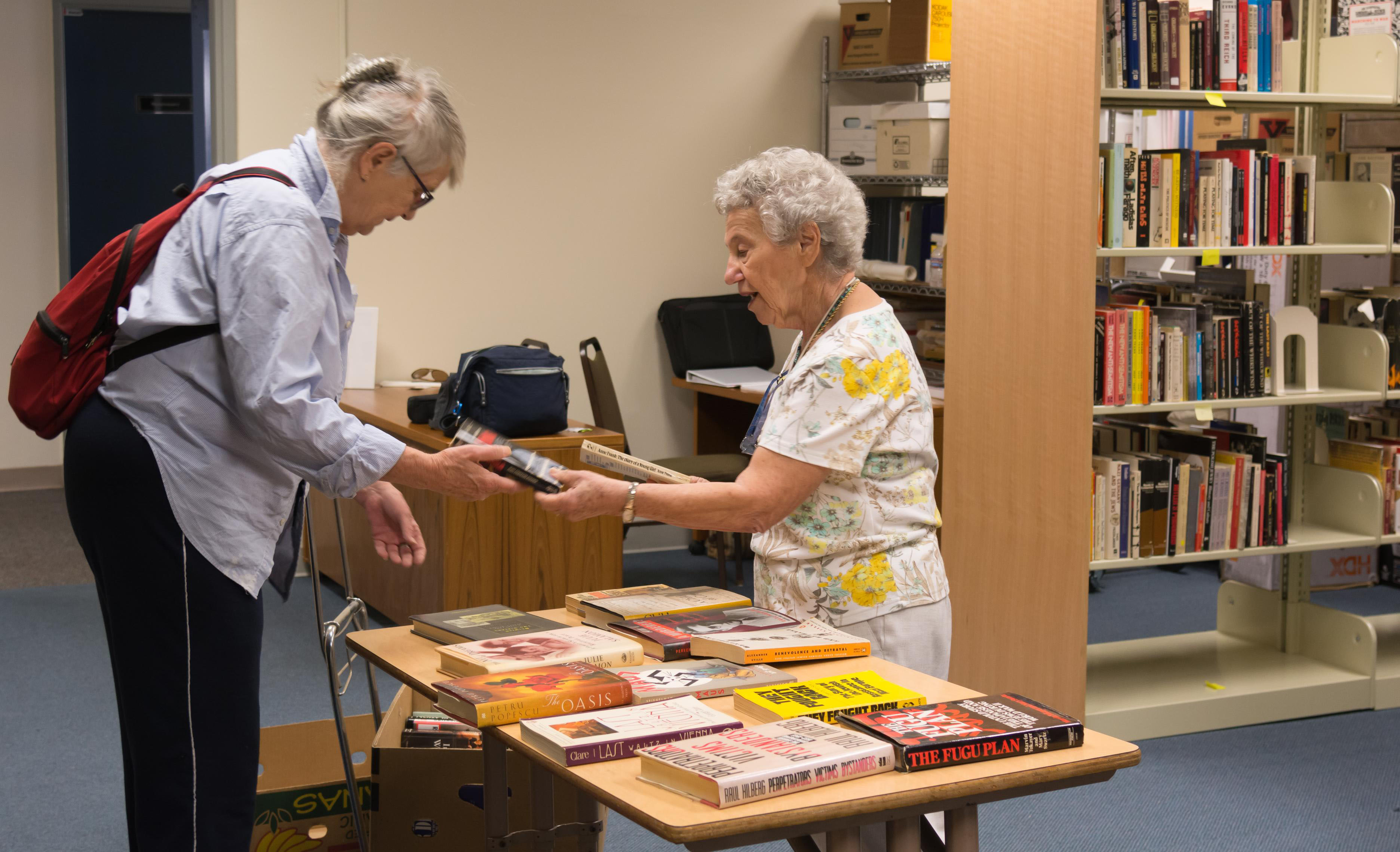 in a library, one old woman hands another woman a book