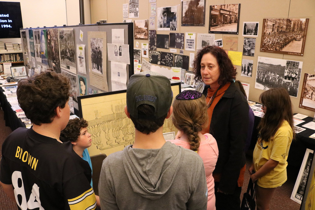 Bendahan speaks with a small group of students, with exhibits arrayed behind her