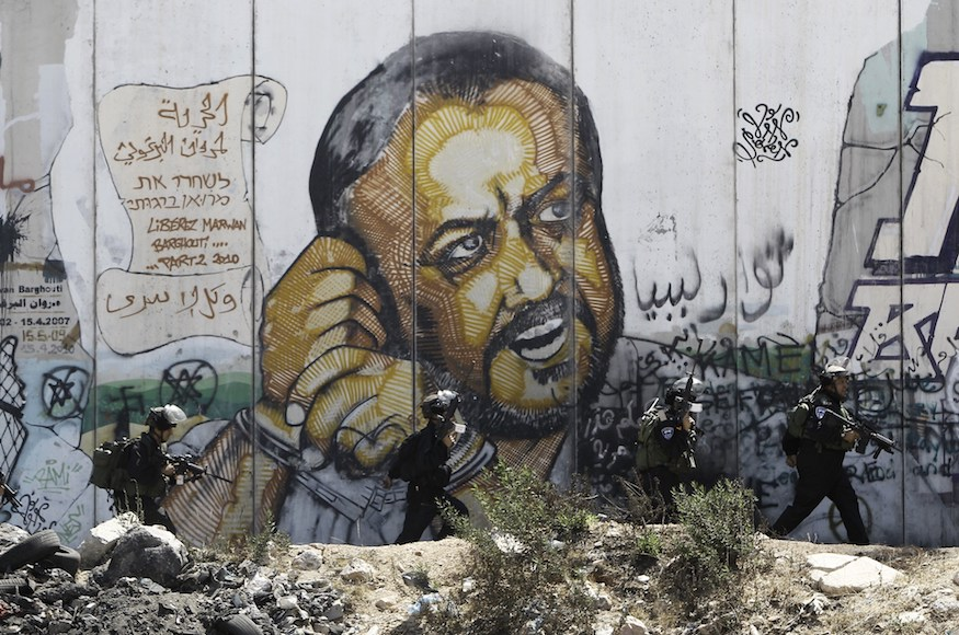 Israeli soldiers walk past a mural that depicts Barghouti with his hands cuffed