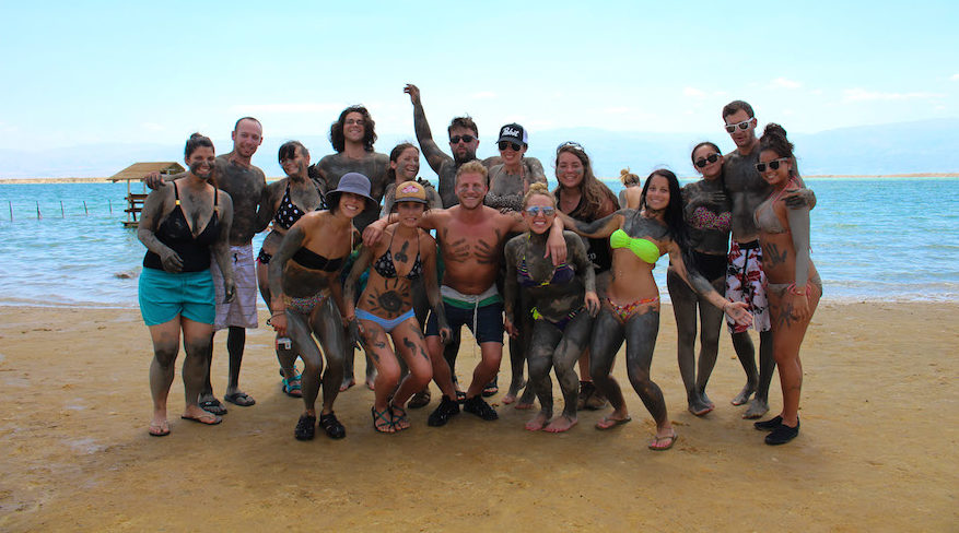 a group of young Jews pose covered in dead sea mud