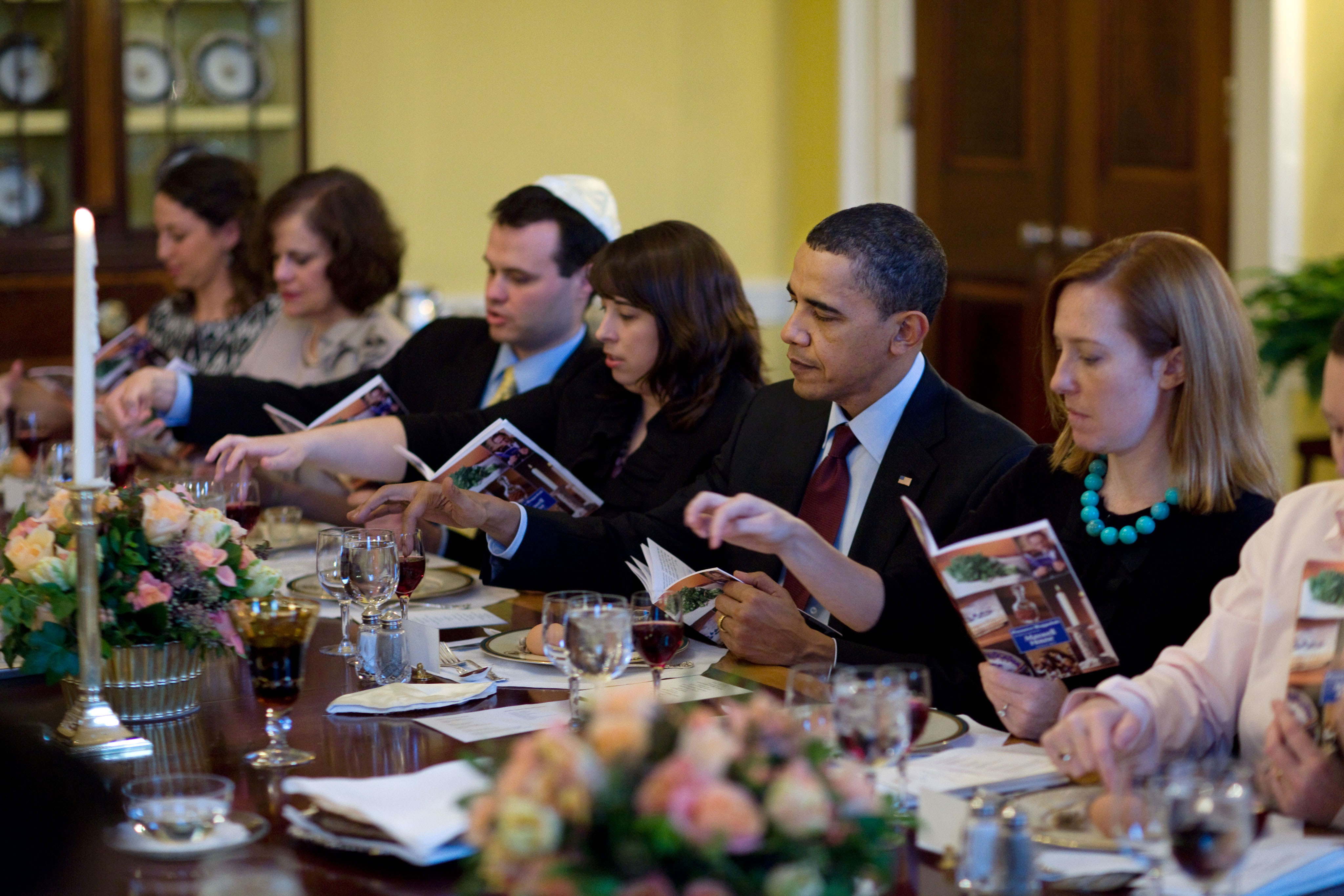 Obama and guests dip their fingers in wine to recite the ten plagues