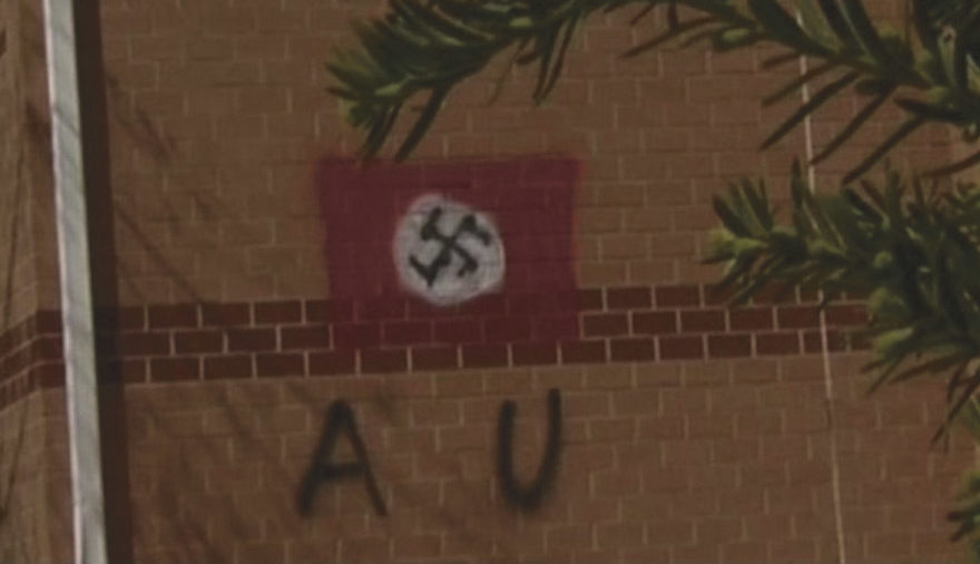 a red and white flag with a swastika painted on a brick wall with the letters A and U