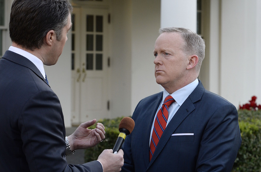a reporter holds a microphone up to sean spicer