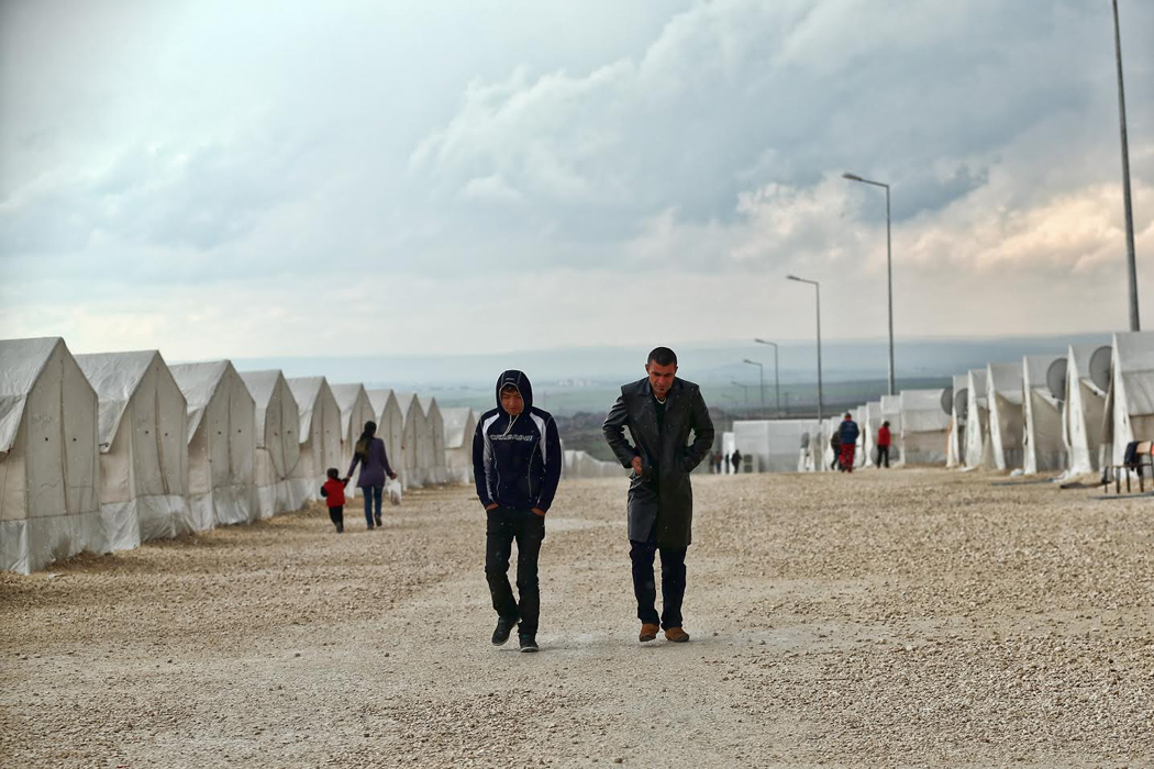 two men walk through bleak rows of small white tents