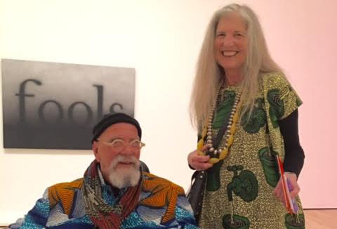 Garchik and Close are wearing particularly colorful, loud outfits in an art gallery