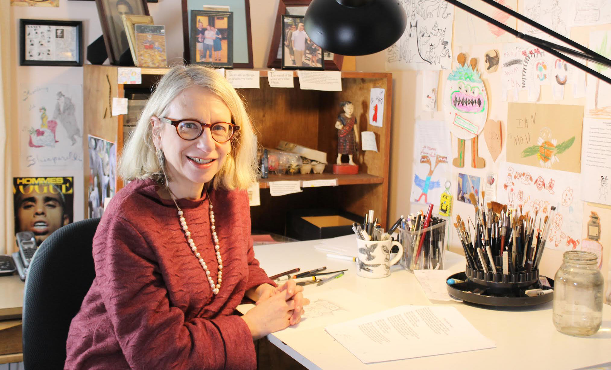 Roz Chast in her studio, surrounded by her cartoons and photos of her family