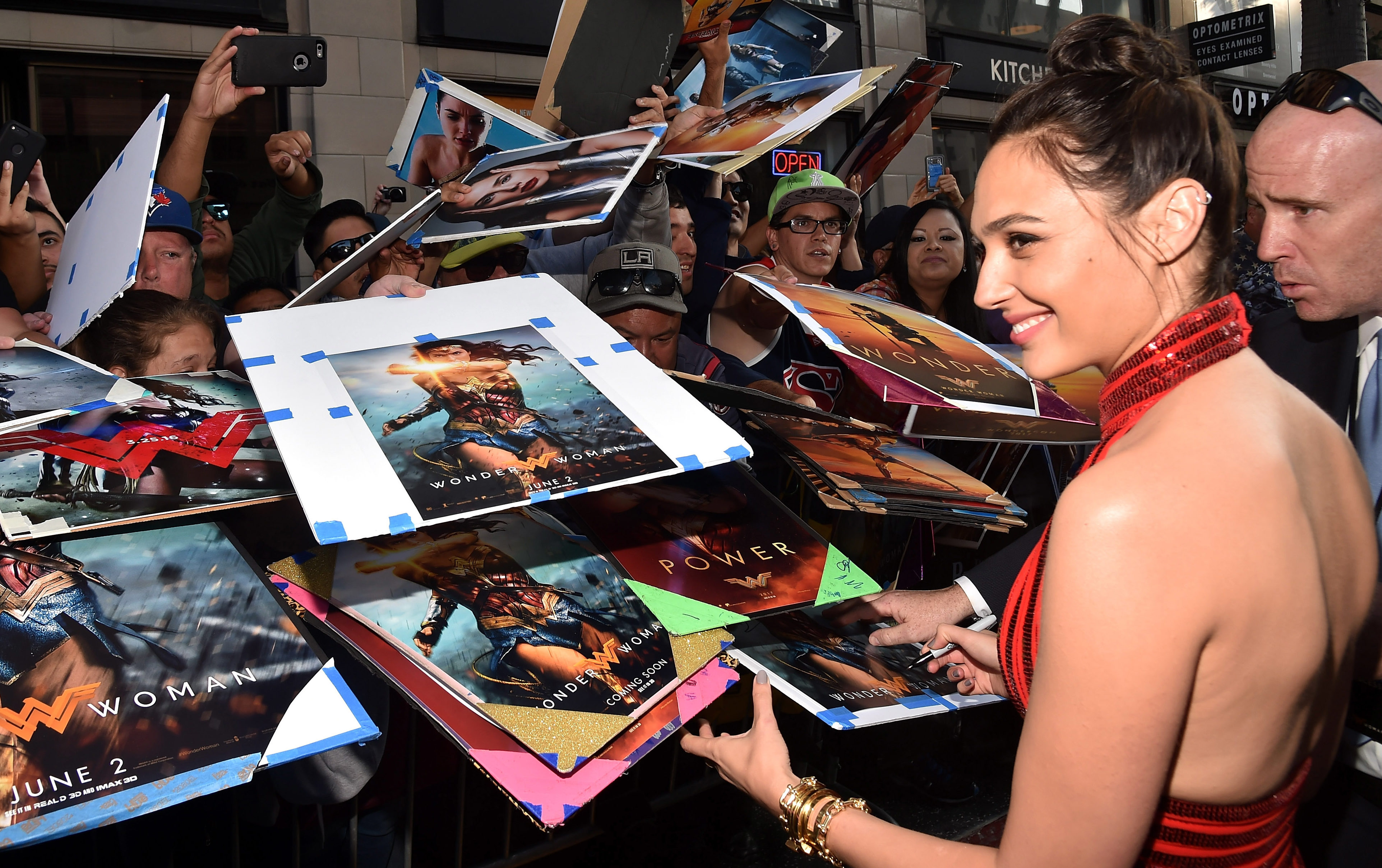 Gal Gadot signs posters for hordes of adoring fans