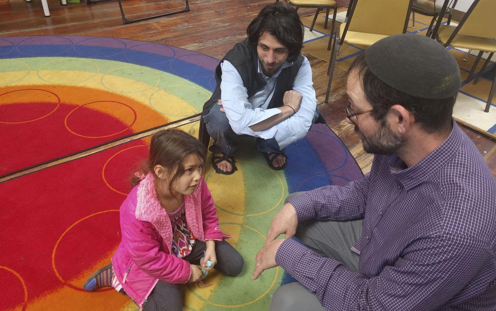 the three sit talking on a bright rainbow rug