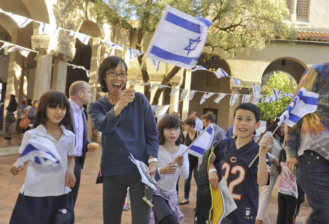 a family waves israeli flags ecstatically