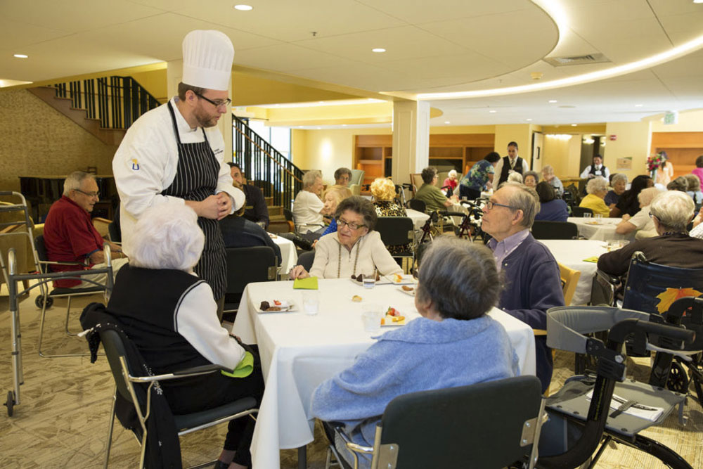 several resident sit around a dining table while a man in chef hat talks to them
