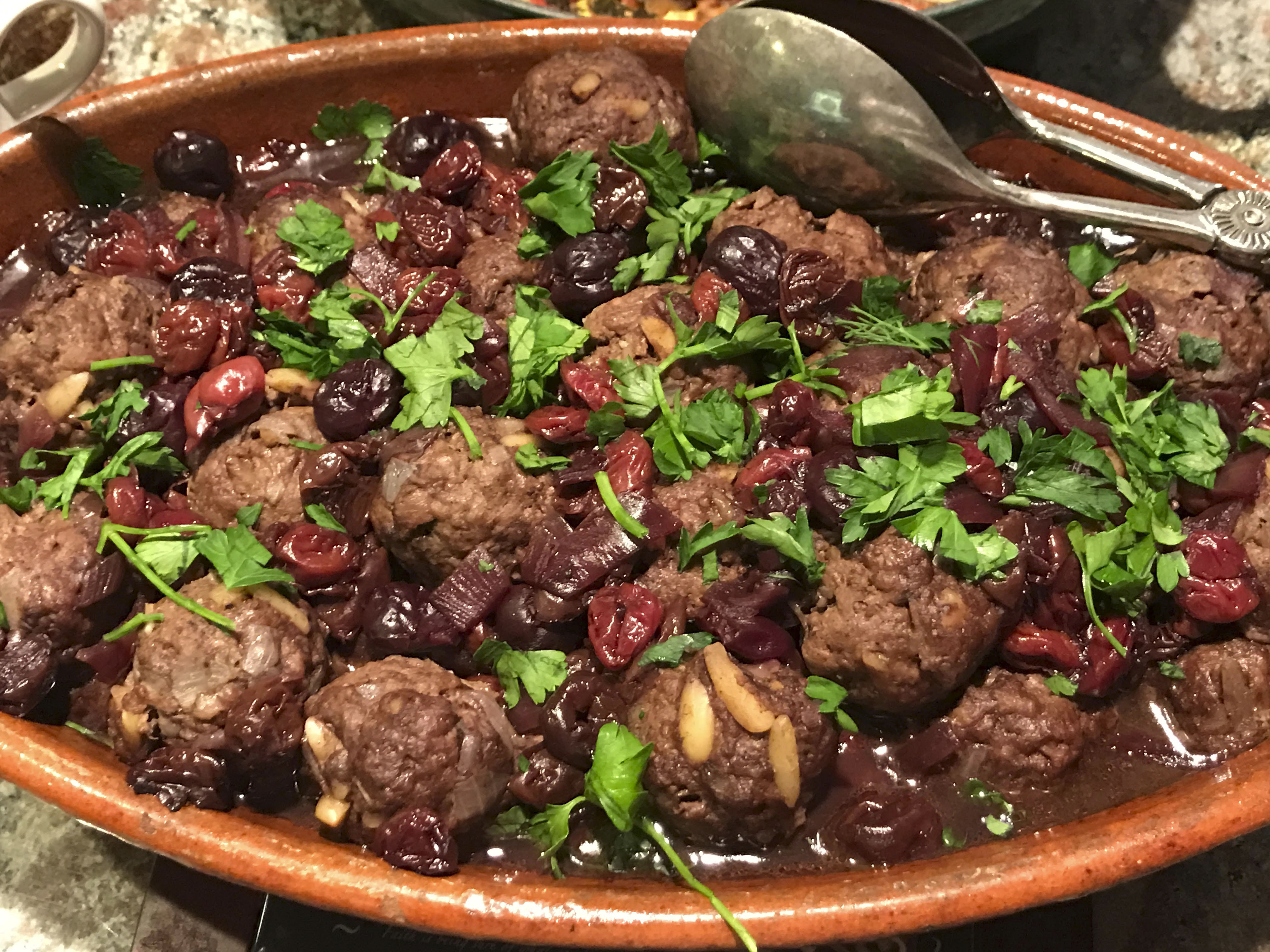 a large pot filled with meatballs and beans, greenery sprinkled on top