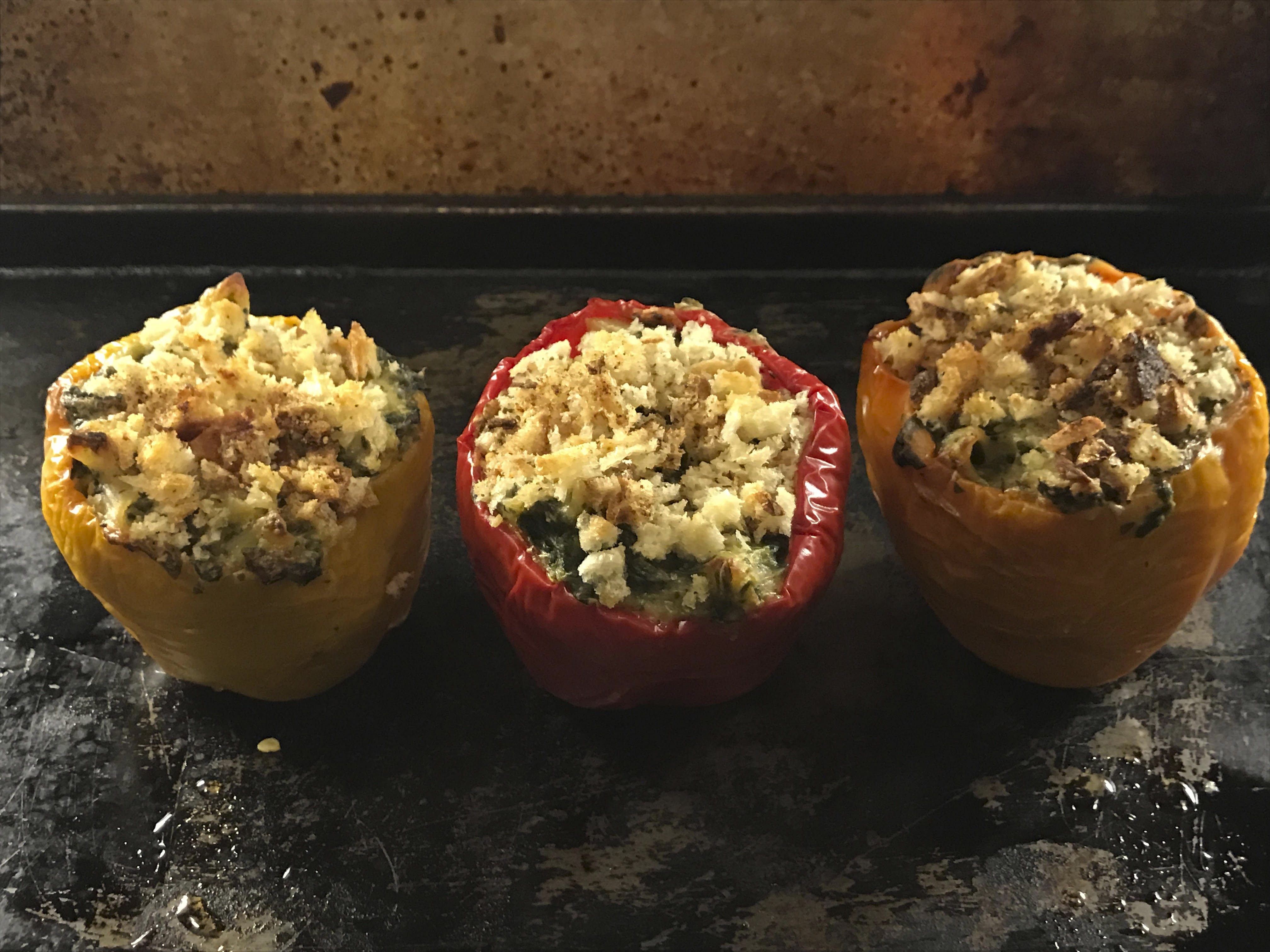 three bell peppers (two red, one yellow), stuffed with mac and cheese