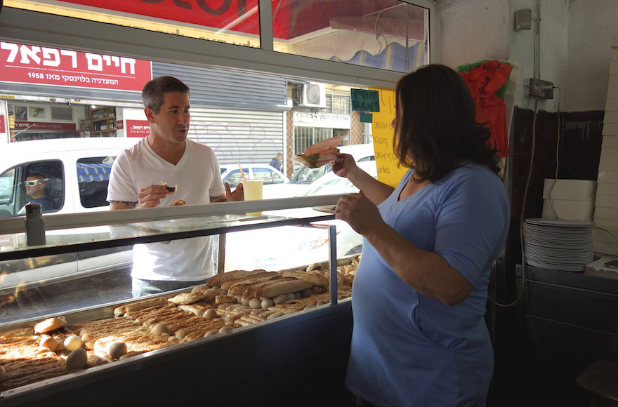 solomov purchases food at a market stall