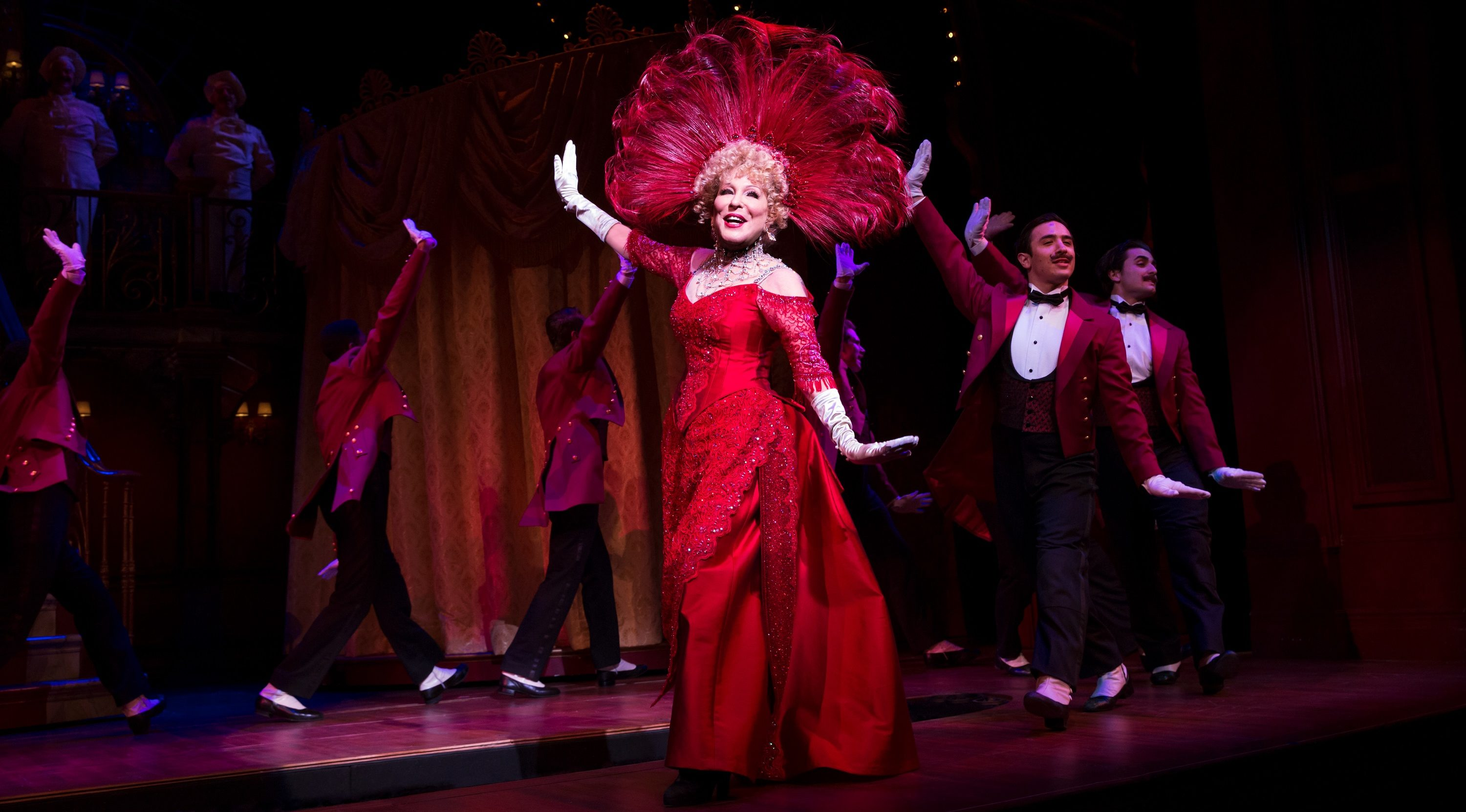 midler dancing in an elaborate red dress and feathered headwear
