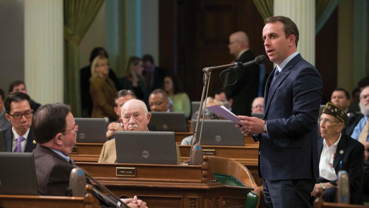 Levine stands speaking before fellow legislators