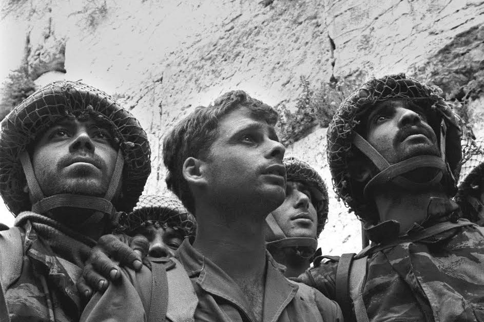 black and white: three men in IDF uniforms gaze up at the wall
