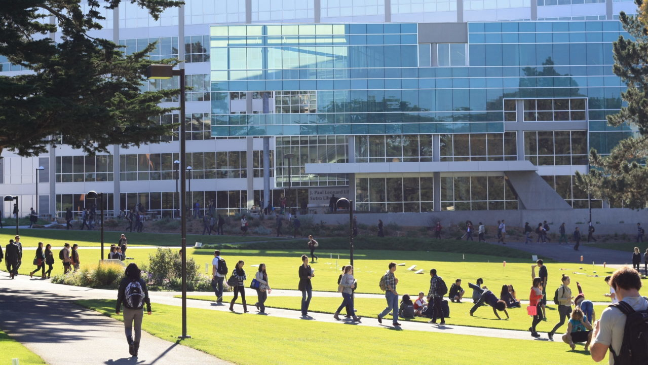 a big glass building with students walking through a lawn in front