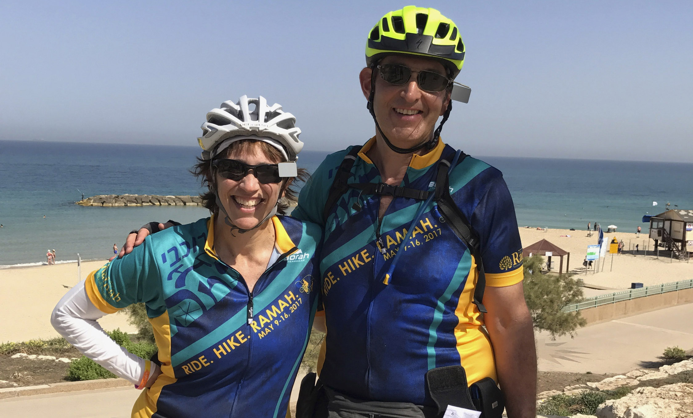 the two stand in pro cycling gear on a beach