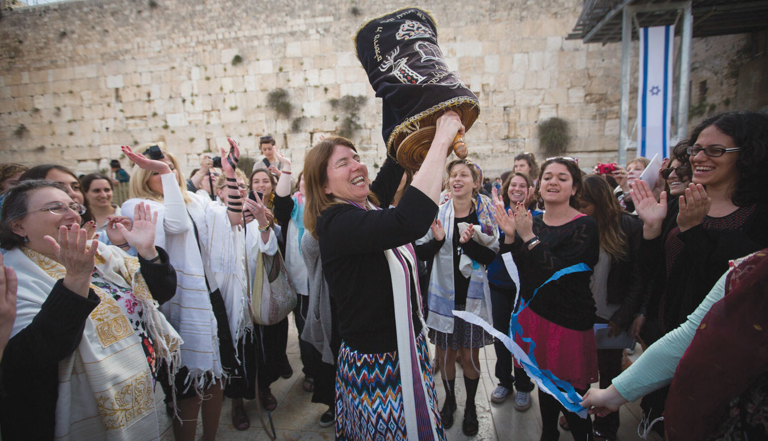 Singer dances in the center of a group of women, smiling and hosting a Torah scroll up over her head