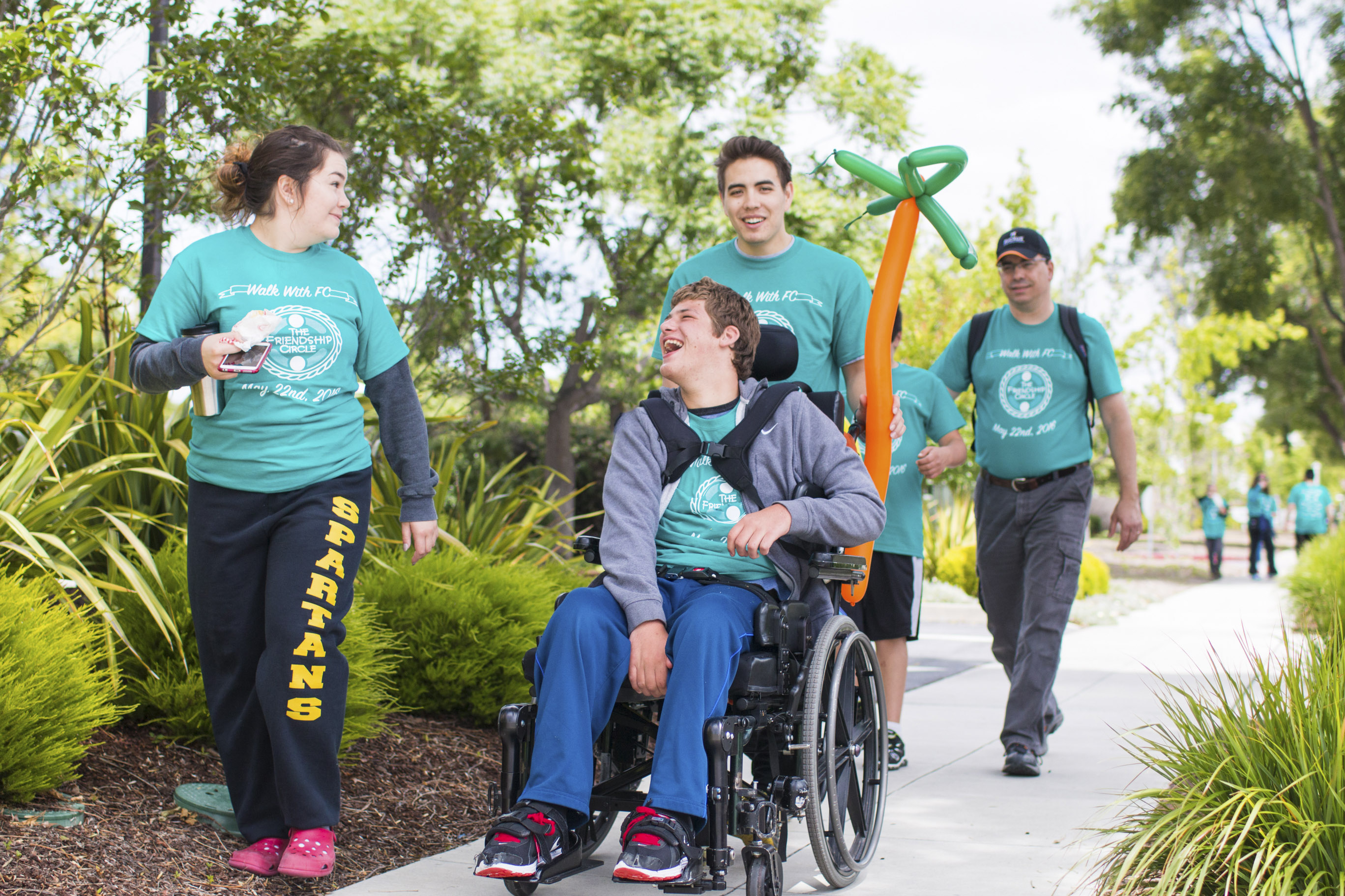 Walk-a-Thon marchers with disabled teen in a wheelchair.