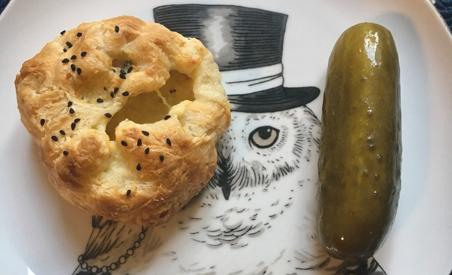a small pastry sits next to a pickle on a plate with an image of an owl in a top hat on it