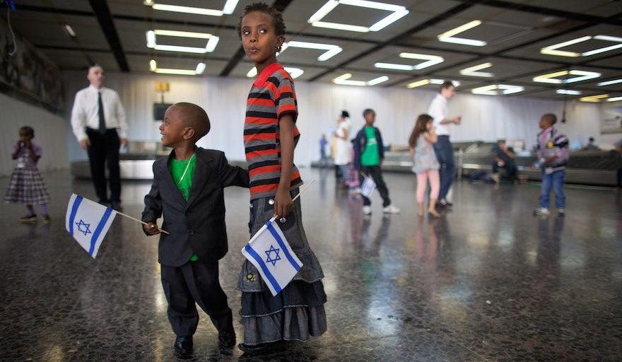 two ethiopian children holding israeli flags